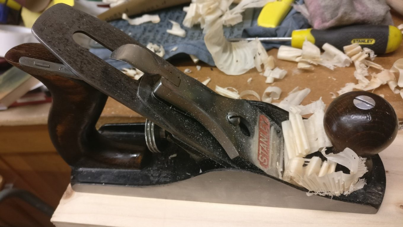 A restored Stanley No. 4 plane cutting a shaving