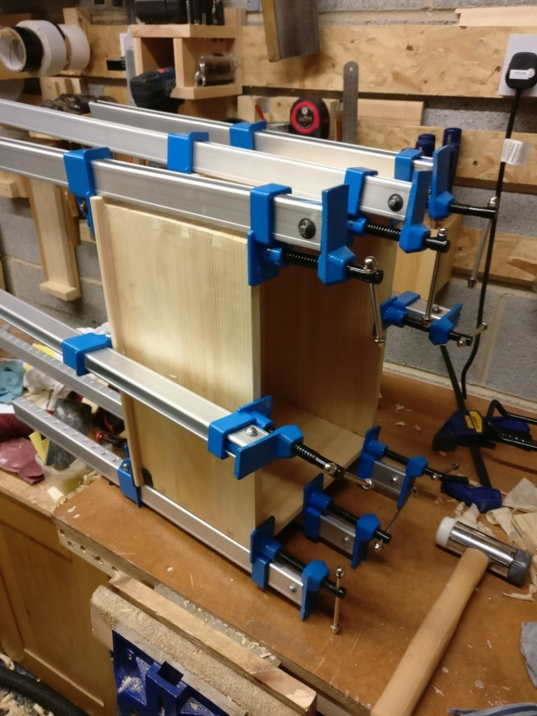 A large pine dovetail box being glued onto its base