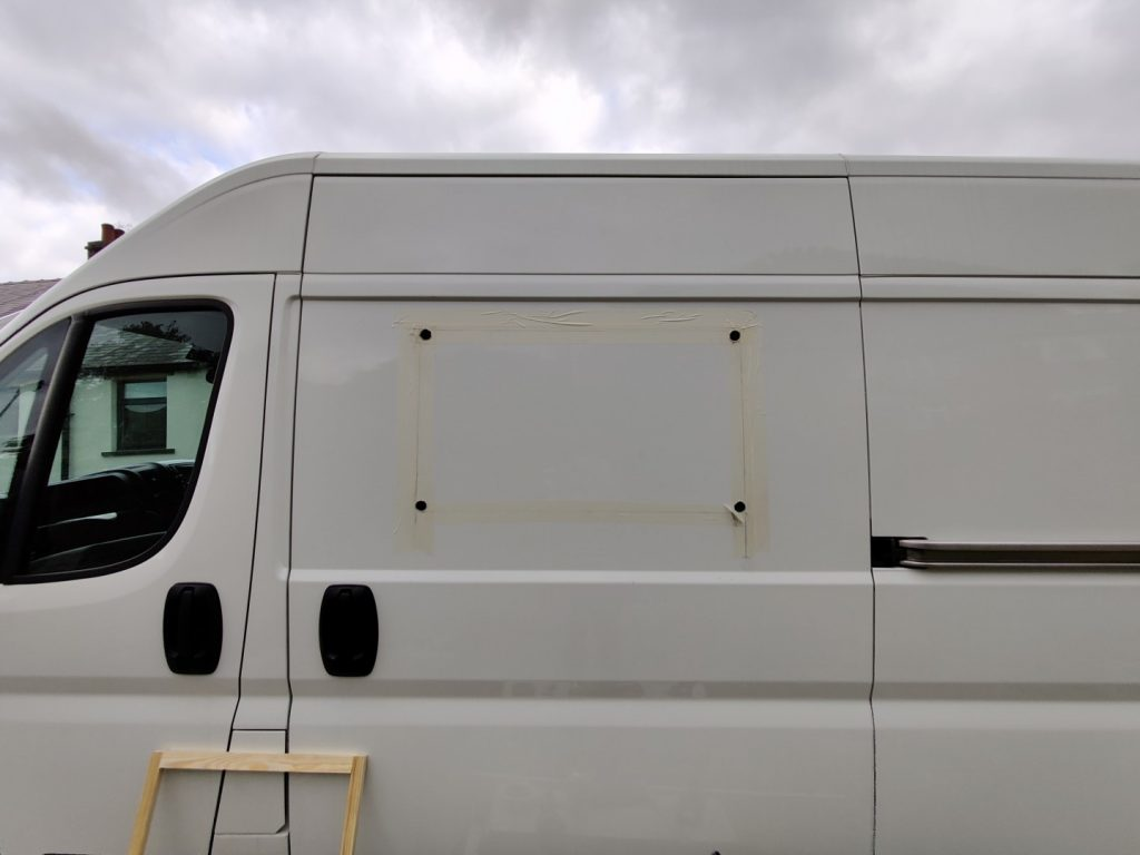The side of the van with four holes cut in the corners of what would become the window opening