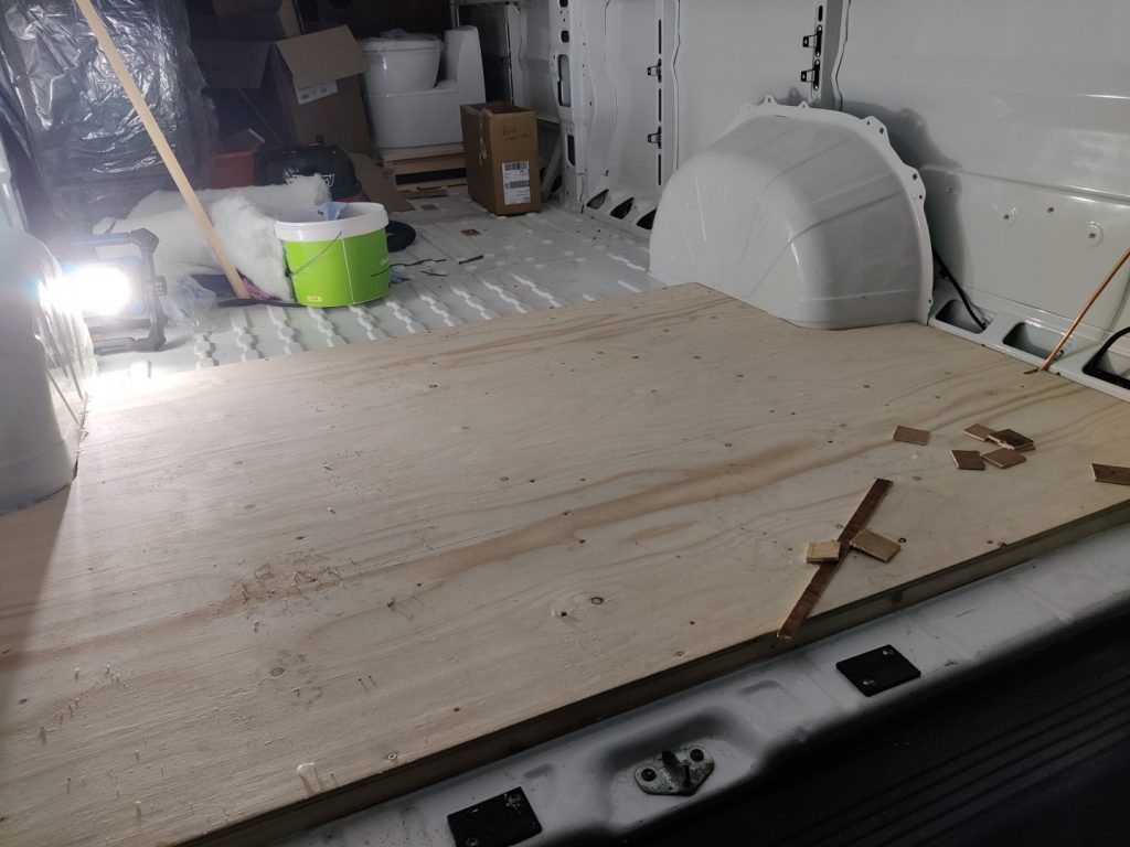 The inside of the van with part of the floor boarded with plywood