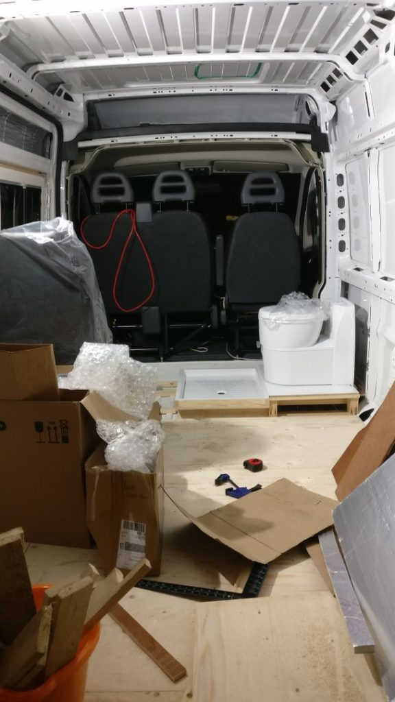 The van floor mostly boarded out, with the toilet and shower tray fitted loosely in place