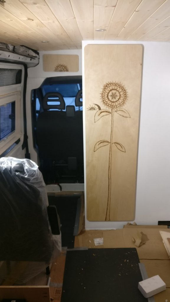The bathroom door, which is made from Birch plywood with a sunflower design that Amy did using pyrography